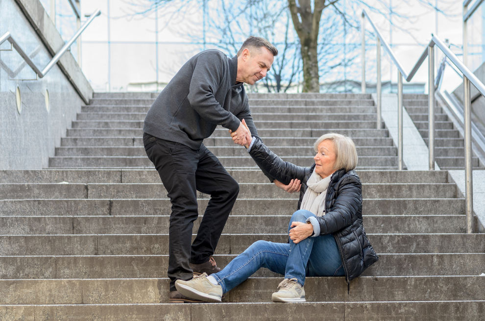 Man helping senior woman get up