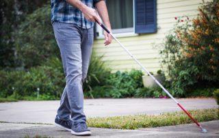 Blind man walking around neighborhood
