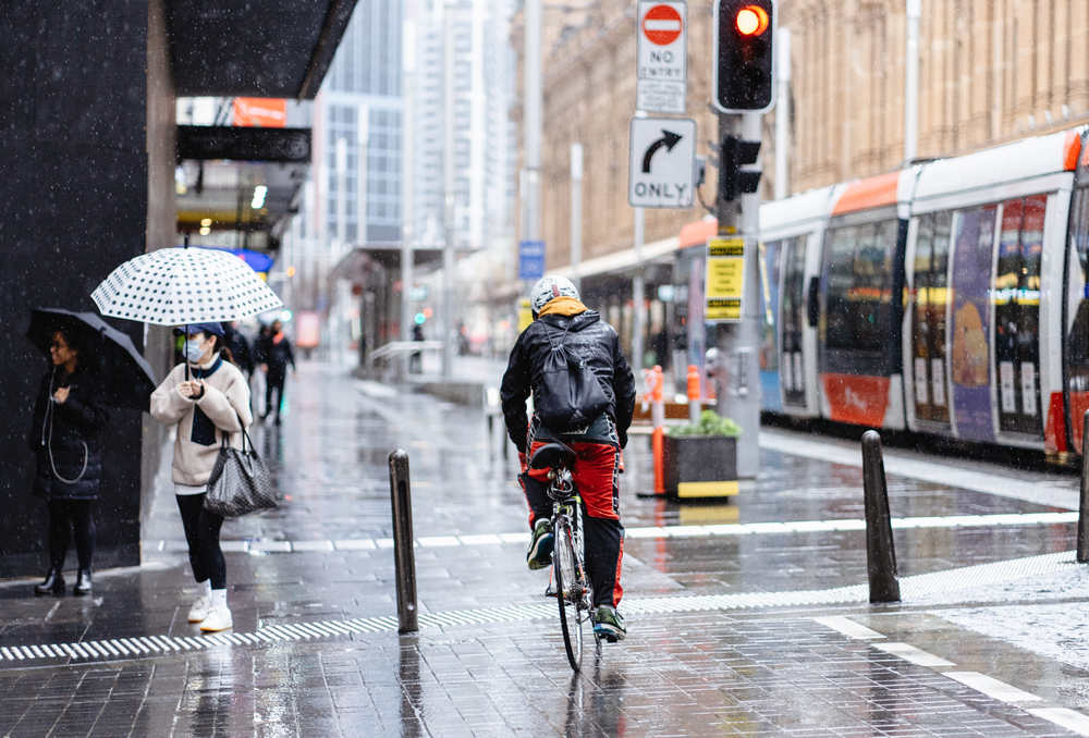 Peson riding bike in the city under the rain (5 Safety Tips For Cycling in the Rain)