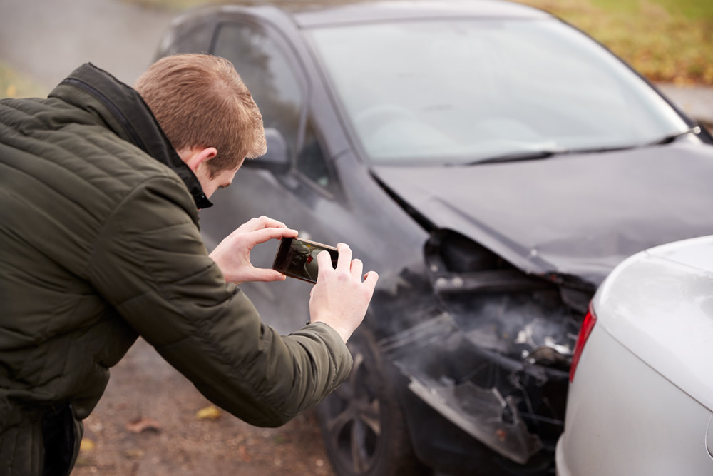 Man Taking Photo Of Car Accident On Mobile Phone